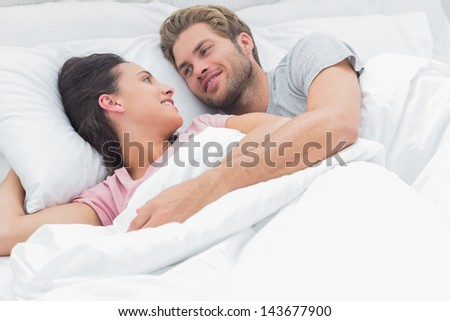 Couple embracing and looking at each other while they are lying in bed - stock photo