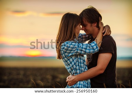 Couple embracing at sunset on the countryside. Young romantic man and woman standing and hugging each other with tenderness during twilight in the field. Young love concept. Instagram effect.