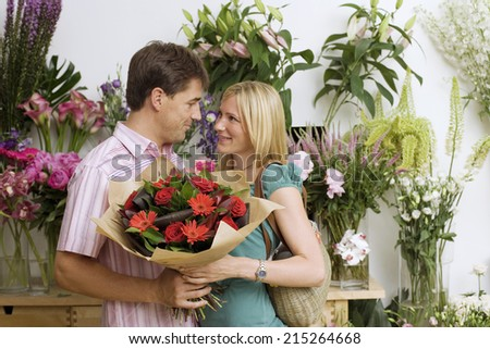 Couple embracing beside display in flower shop, holding bouquet of red flowers, smiling, side view - stock photo