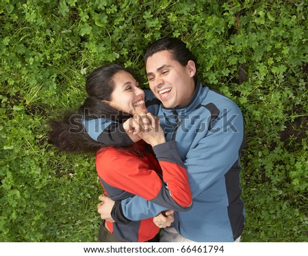 Couple embracing in clover field - stock photo