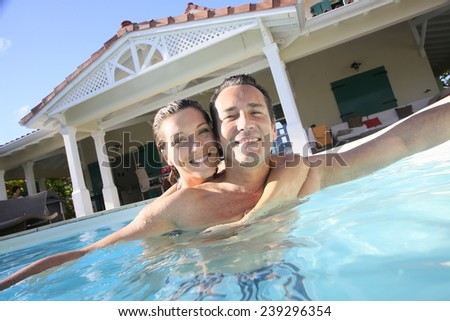 Couple embracing in private swimming pool - stock photo