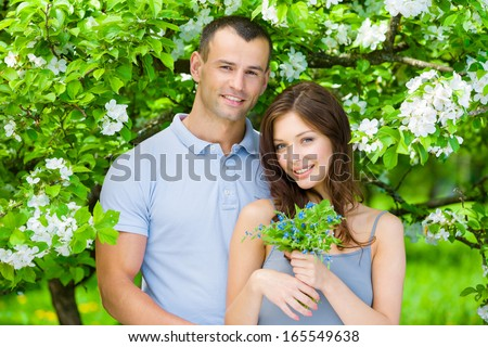 Couple embracing near flowered tree in the park, girl hands flowers. Concept of love and stable relations