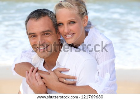 Couple embracing on the beach - stock photo