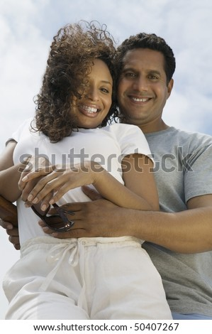 Couple embracing outdoors, (portrait), (low angle view)