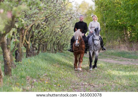 Couple enjoy riding horses in spring garden. - stock photo