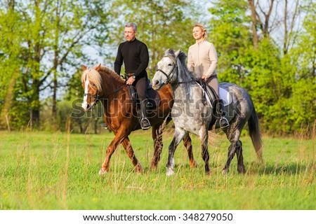 Couple enjoy riding horses in summer meadow. - stock photo