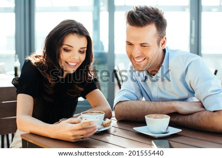 Couple enjoying a coffee and browsing photos on a smartphone - stock photo