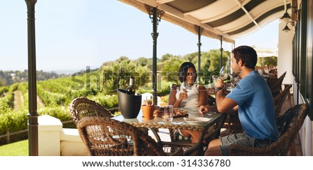 Couple enjoying a glass of wine in a vineyard. Young man and woman drinking white wine while sitting at a table on a wine cellar. - stock photo