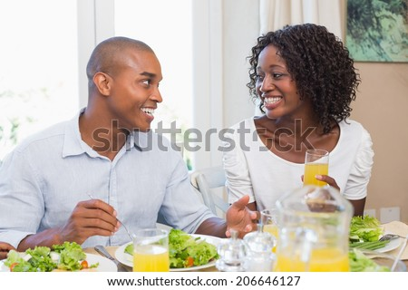 Couple enjoying a healthy meal together smiling at each other at home in the kitchen