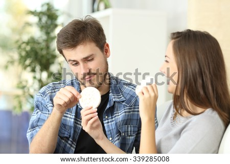 Couple enjoying and suffering diet with girlfriend offering a dietetic cookie and the boyfriend disgusted - stock photo