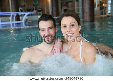 Couple enjoying bath in spa center jacuzzi - stock photo