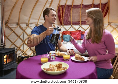 Couple Enjoying Breakfast Whilst Camping In Traditional Yurt - stock photo