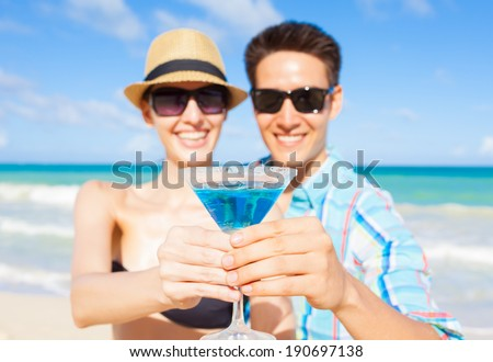 Couple enjoying cocktail on the tropical beach in Hawaii, USA. - stock photo