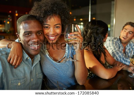 Couple Enjoying Drink At Bar With Friends - stock photo