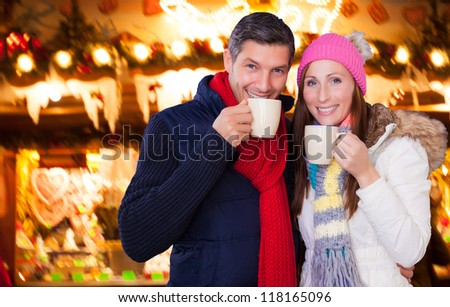 couple enjoying hot wine punch claret on christmas market