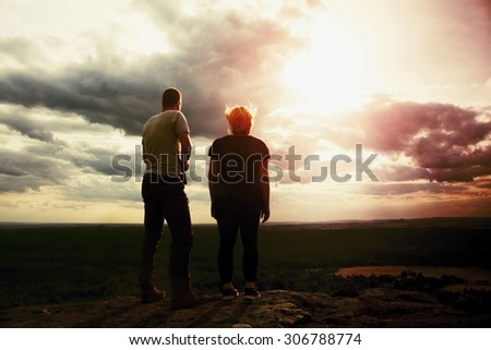 Couple enjoying marvellous moments during sunset . Young pair of hikers on the peak of rock empires park and watch over valley to Sun. Soft effect. - stock photo