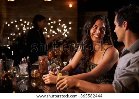 Couple Enjoying Night Out At Cocktail Bar - stock photo