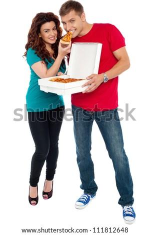 Couple enjoying pizza together, great bonding. Full length shots - stock photo