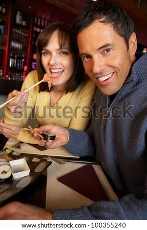 Couple Enjoying Sushi In Restaurant - stock photo