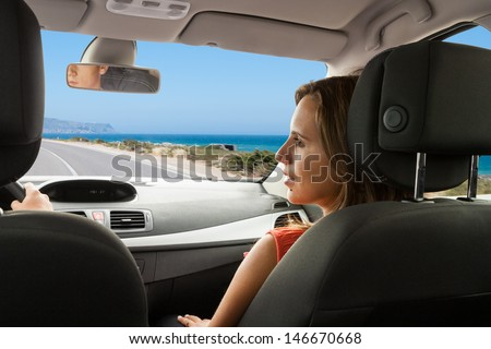 Couple enjoying their new car on a coastal road - stock photo