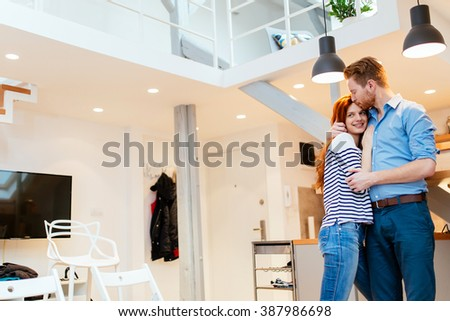 Couple enjoying their new luxurious home and hugging in living room - stock photo