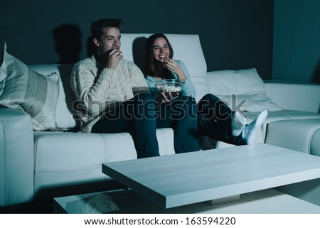 Couple enjoying watching a movie at home laughing on the couch - stock photo