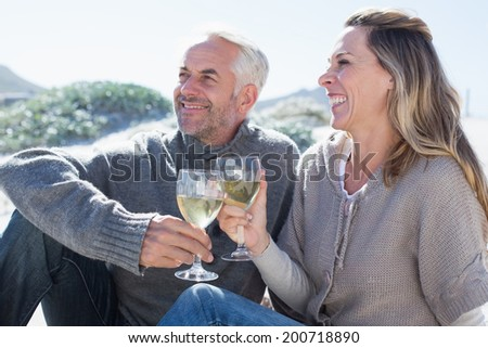 Couple enjoying white wine on picnic at the beach on a bright but cool day - stock photo