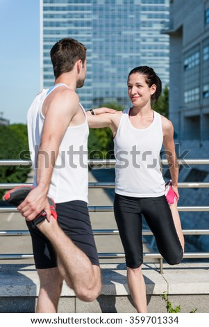 Couple exercising and stretching muscles before sport activity in city - stock photo