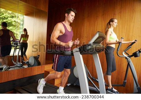 Couple Exercising Together In Home Gym - stock photo