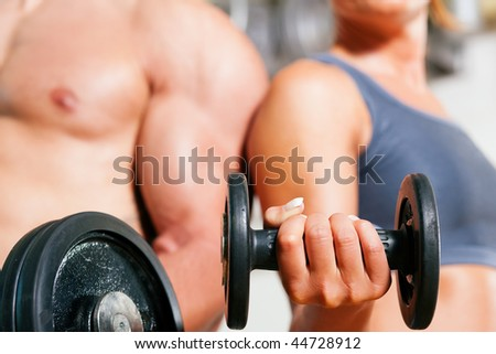 Couple exercising with dumbbells in a gym, focus on the weights, only torso of man and woman to be seen - stock photo