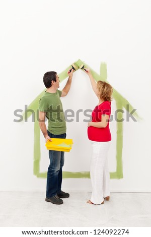 Couple expecting a baby - painting their new home - stock photo