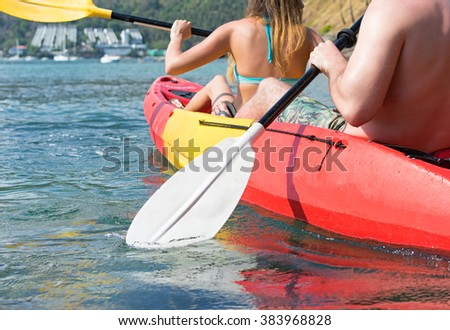 Couple exploring calm tropical bay by kayak.  Back view.  - stock photo