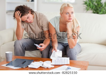Couple figuring out what to do sitting in the livingroom - stock photo