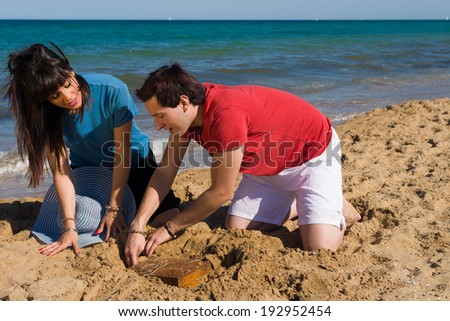 Couple finding a  a chest with a treasure on the beach - stock photo