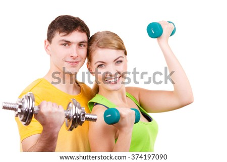 Couple fit woman and strong man exercising with dumbbells. Muscular guy and fitness blonde girl lifting weights. Bodybuilding. - stock photo