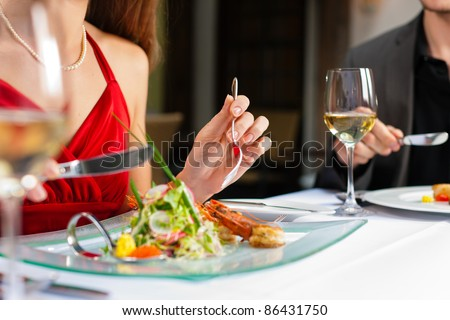 Couple for romantic Dinner or lunch in a gourmet restaurant drinking wine and eating - stock photo