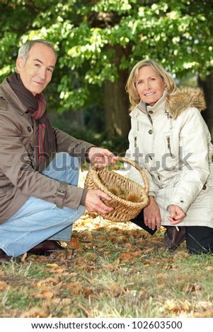 Couple foraging in the woods - stock photo