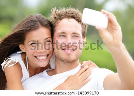 Couple fun taking self-portrait picture photos with mobile smart phone or pocket camera outdoors. Happy multiracial young couple in love taking pictures together on summer vacation. Man and woman - stock photo