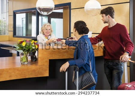 Couple giving passports to receptionist at counter in hotel - stock photo