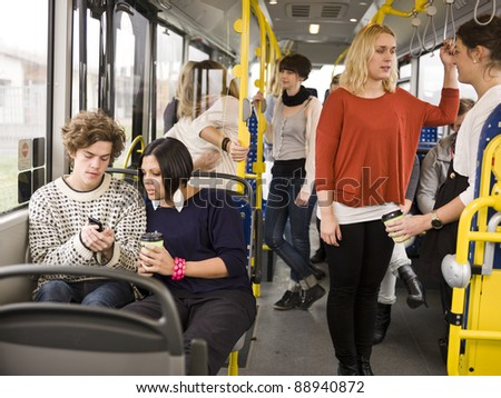 Couple going by bus with large group of people - stock photo