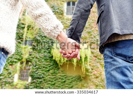 Couple hand in hand with autumn clothes and colored leaves background.