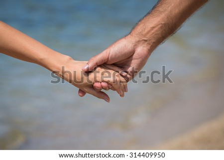 Couple hands against the sea view, close up