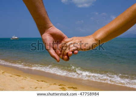 Couple hands in a sky and sea close-up