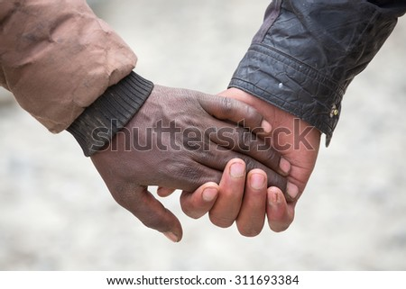 Couple hands  on the street in India, close up. In India, it is normal to go to men holding each other by the hand - stock photo