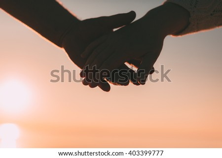 Couple hands reach silhouette on a sky and sea background. Evening photo.