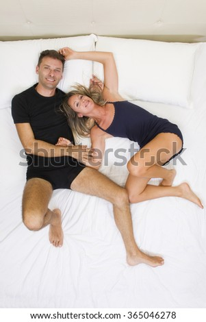 Couple happy and smiling, holding hands on the bed top view - stock photo