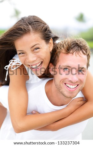 Couple happy having fun piggybacking and laughing outdoors during summer holidays travel vacation. Happiness concept with interracial couple, Asian woman and Caucasian man. - stock photo