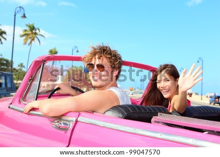 Couple happy in vintage retro convertible car. Friends driving on summer road trip in pink car. Beautiful young Caucasian man and Asian woman smiling joyful on sunny summer day traveling. - stock photo