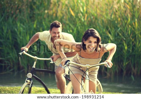 Couple having a bicycles race into the nature - stock photo