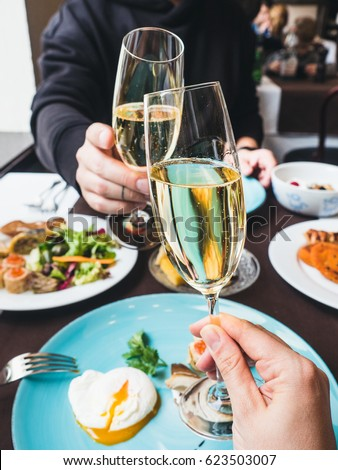 Couple having a brunch with sparkling wine in a fancy hotel or restaurant. Glasses of sparkling wine in hands, cheers!  Benedict  egg and other food on a background